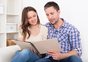 Couple Sitting On Couch Looking At Photo Album