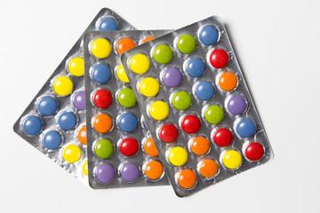 Farbige Tabletten auf weißem Hintergrund