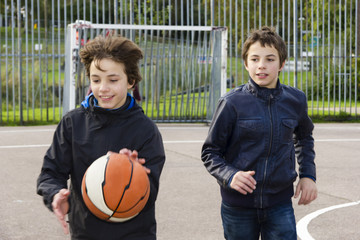 Two boys playing basketball  in the playground