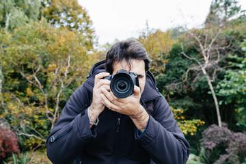 Fotografo in un parco durante un servizio fotografico