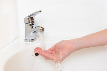 Close-up of human hands being washed under faucet in bathroom,