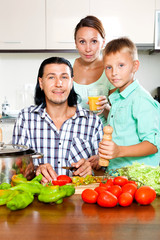 Happy family cooking veggy lunch
