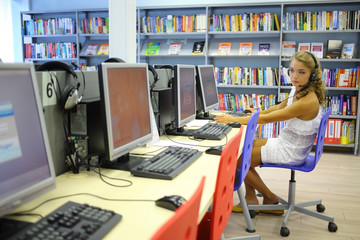 A girl looks into a nearby computer at the library