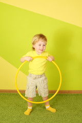Little blond boy in a yellow t-shirt and shorts