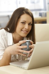 Portrait of happy woman with tea and laptop