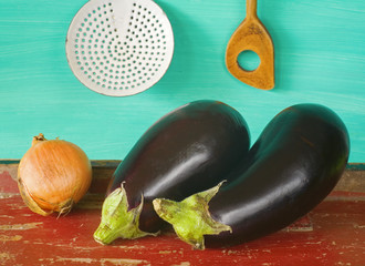Two eggplants with vintage kitchen utensils