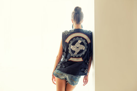 Girl turned a back in leather vest