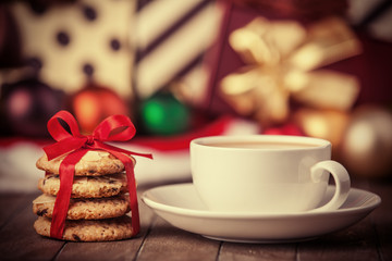 Cookies, cup of coffee with christmas gifts at background