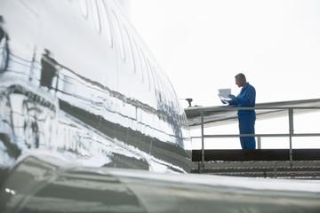 Engineer reviewing paperwork at tail of passenger jet in hangar