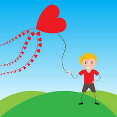 Smiling boy with a kite in the shape of heart