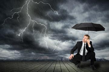 Mann im Anzug und Regenschirm sucht Schutz vor Unwetter