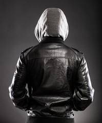 Young man in leather jacket and hood rear view