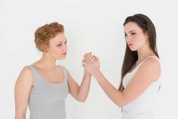 Two serious young female friends arm wrestling