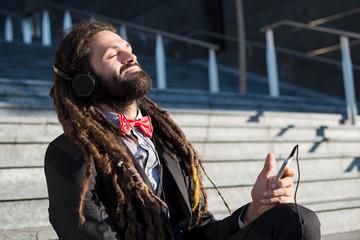 Stylish elegant dreadlocks businessman listening music