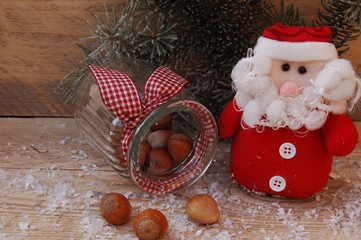 Weihnachtsmannfigur mit Haselnüssen und Tannenzweig