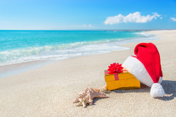 Santa Claus hat and christmas gift box on the seashore with sea