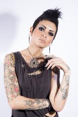 Tattooed punk girl posing on white background