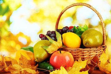 Different fruits and vegetables with yellow leaves in basket