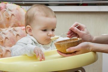 Мама кормит своего маленького ребёнка с ложки