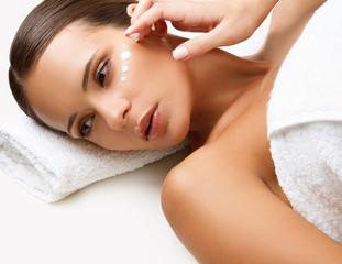 Wall Mural - Beautiful Woman Getting Spa Treatment. Cosmetic Cream on a Cheek