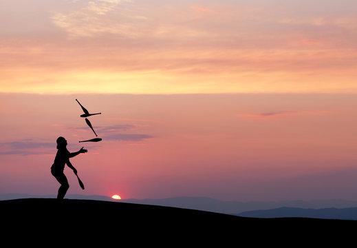 silhouette of juggler in sunset