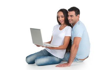 Indian couple sitting with laptop.