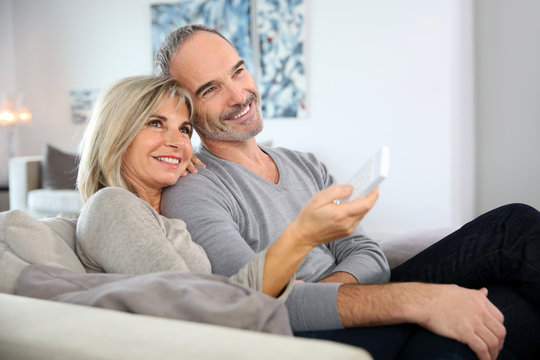 Senior couple sitting in couch and watching tv