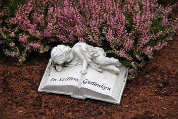 Friedhof - Auf Buch ruhender Engel neben Heidekraut