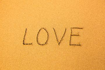 Love - text written by hand in sand on a beach.
