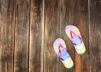 colorful flip flops on wooden deck. summer background