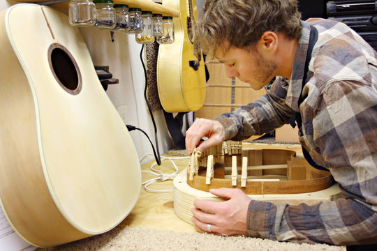 Woodworker Building Guitar in Workshop