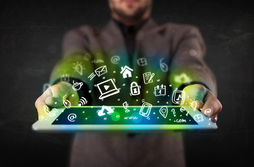 Person holding tablet with green media icons and symbols