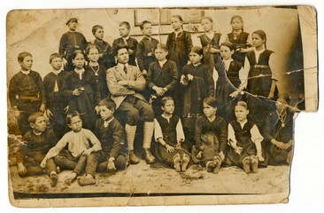 CIRCA 1930: Classmates with teacher