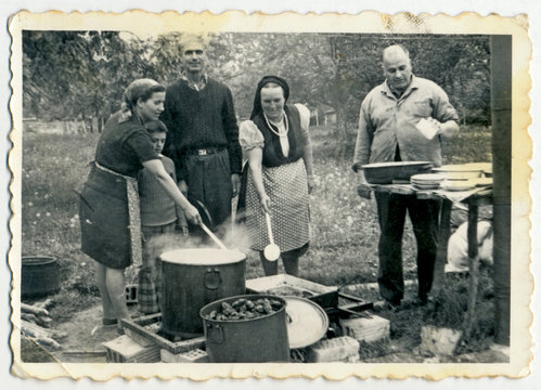 CIRCA 1960: A group of people preparing food on fire in big pots