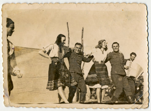 CIRCA 1945: Celebration, women and men (young soldiers) dancing.