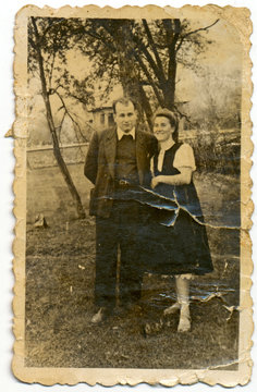 CIRCA 1945: A couple of young people standing near a tree