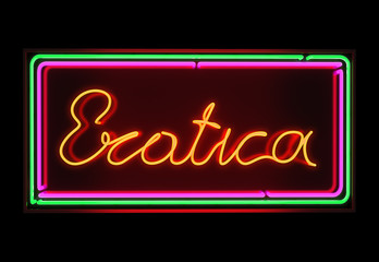 Erotica neon sign illuminated over dark background