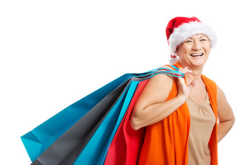 An old woman holding presents/bags in santa hat.