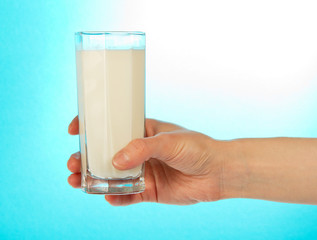 The female hand holds a full glass of milk