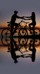 two mountain biker silhouette in sunrise drawn to each other wit