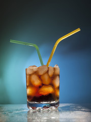 glass transparent glass with ice cubes and Coke with a green and