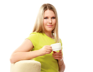 A college girl sitting on an armchair and holding cup of coffee