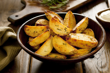 fried rosemary potato wedges in a rustic setting.
