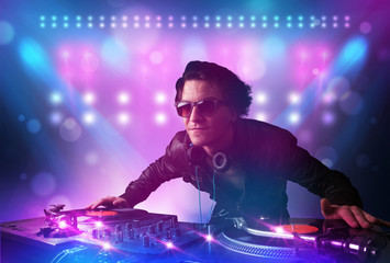Disc jockey mixing music on turntables on stage with lights and