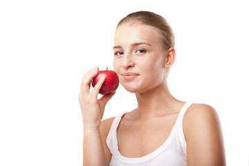 Smiling blond woman eating red apple on white