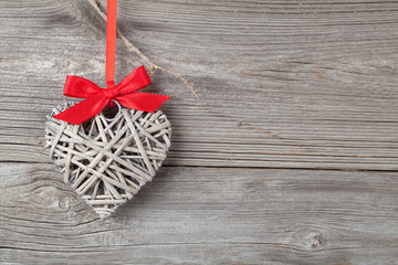 one heart with red bow, on wooden background