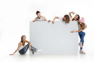 Obraz Grupa młodych ludzi trzyma  pusta białą tablicę - fototapety do salonu