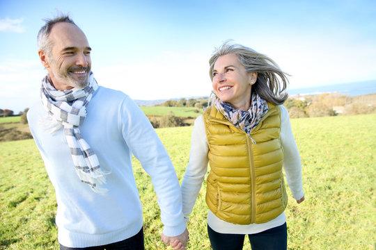 Cheerful senior couple running in countryside
