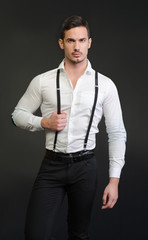 Elegant young man with white shirt and suspenders, serious