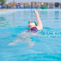 Woman in goggles swimming back crawl style